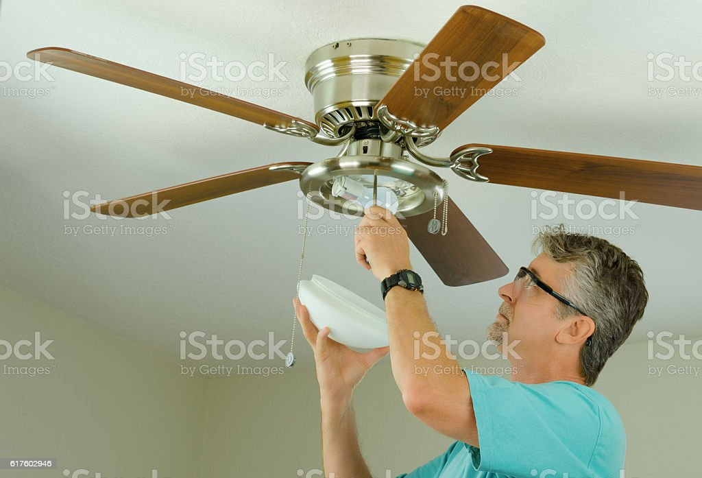 Professional or DIY home owner doing ceiling fan repair work stock photo