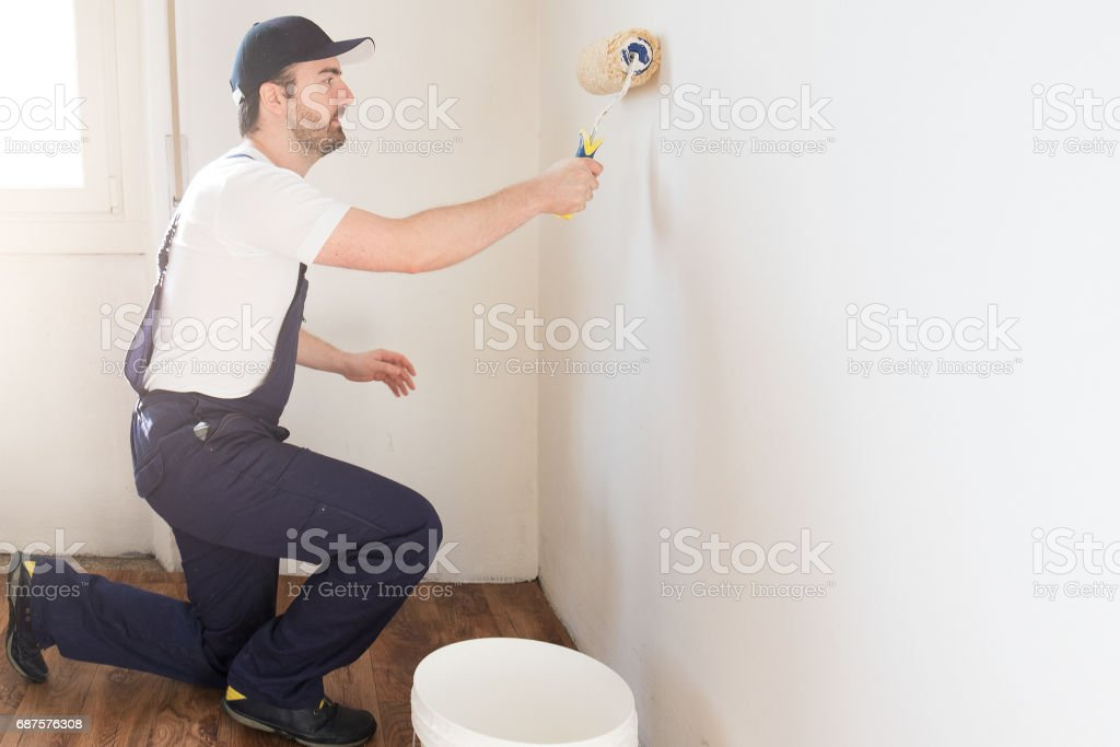 Professional painter worker is painting one wall stock photo