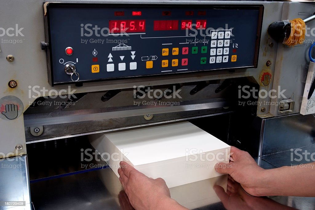 Professional paper cutter machine and stacked paper at printing plant stock photo