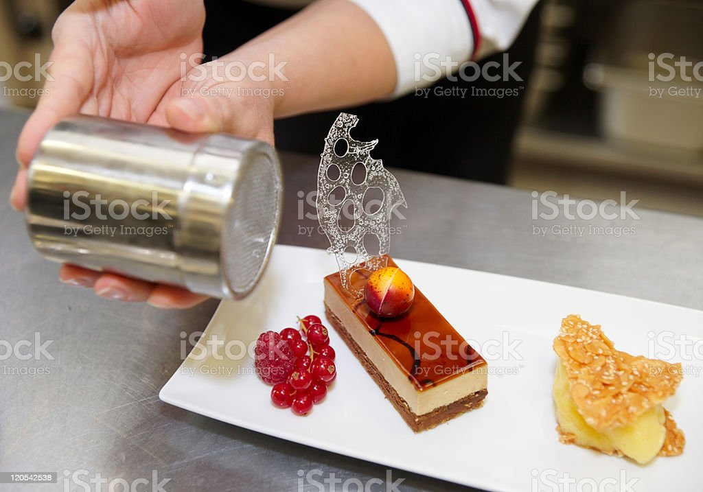 Professional pastry chef is decorating a dessert royalty-free stock photo