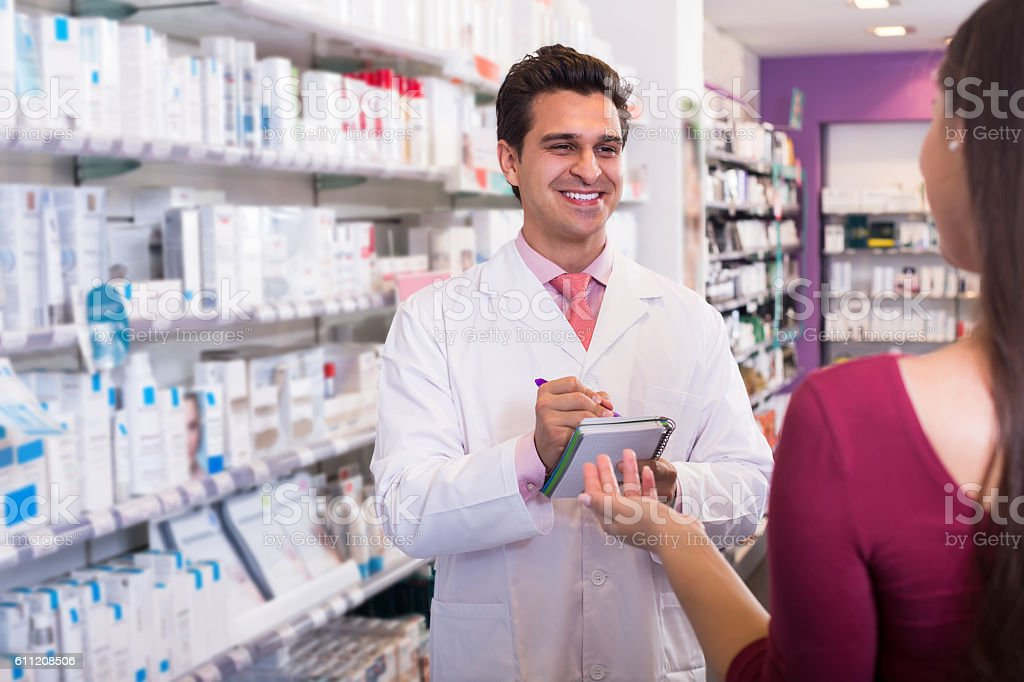 Professional pharmaceutist in drugstore helping girl stock photo