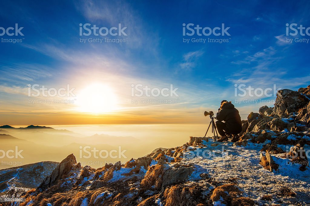 Professional photographer takes photos with camera on tripod stock photo