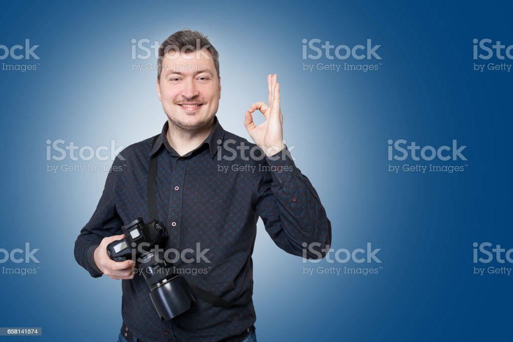 Professional photographer with camera shows ok stock photo