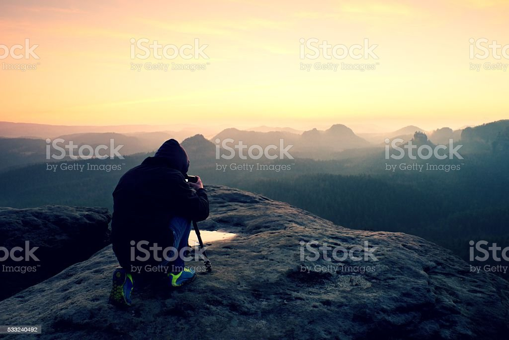 Professional photographer with tripod on cliff and work. Dreamy landscape stock photo