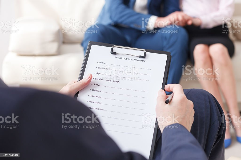 Professional psychologist making notes on therapy session stock photo
