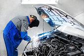 professional repairman worker in automotive industry welding metal body car