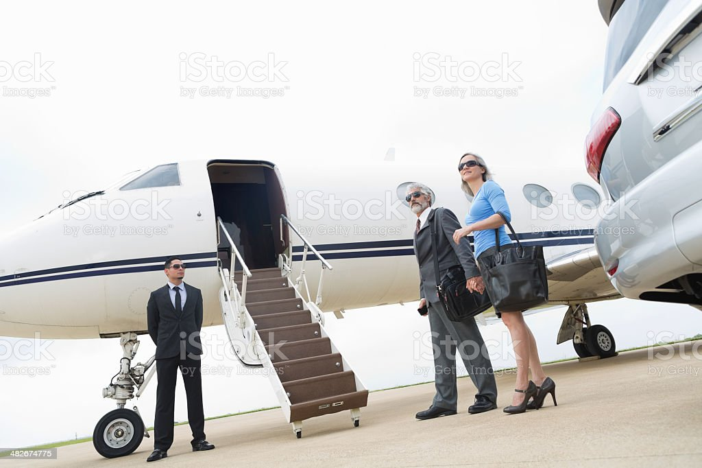 Professional senior couple boarding luxurious private jet stock photo