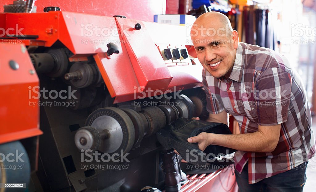 Professional skilled craftsman polishing footwear on machine stock photo