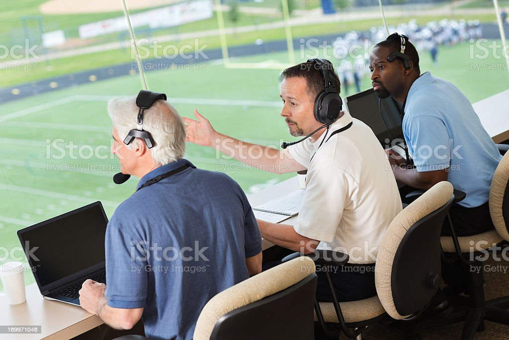 Professional sports commentators in press box at football game stock photo