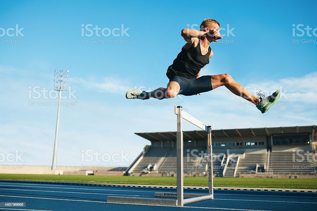 Professional sprinter jumping over a hurdle stock photo
