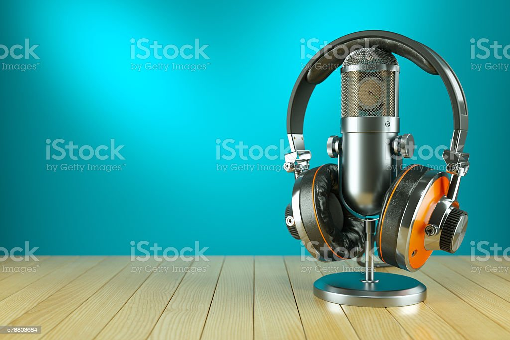Professional studio microphone and headphones on wooden table stock photo