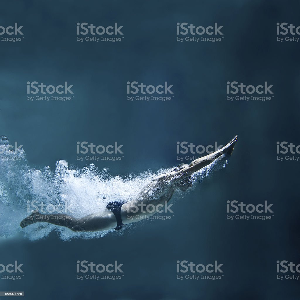 professional swimmer underwater after the jump stock photo