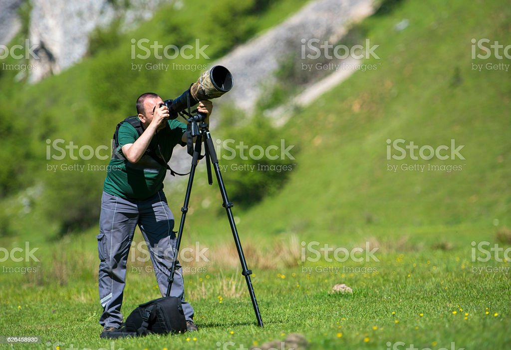 Professional travel on location and nature videographer/photographer (man) photographing stock photo