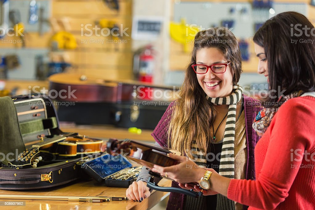 Professional violinist has violin repaired in musical instrument repair shop stock photo