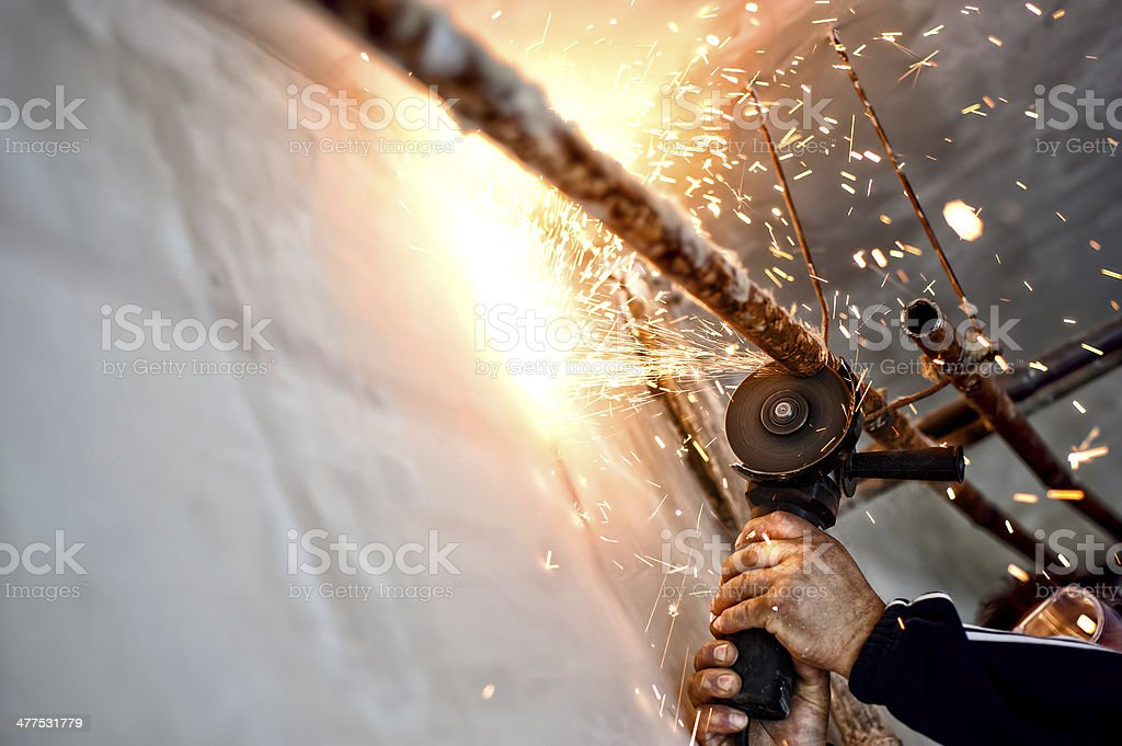 Professional welder cutting and grinding metal pipes stock photo