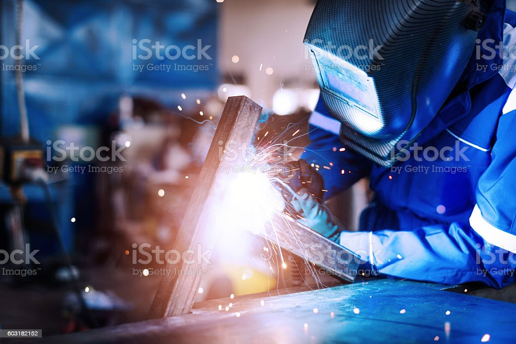 Professional welder in a factory welding steel bars stock photo