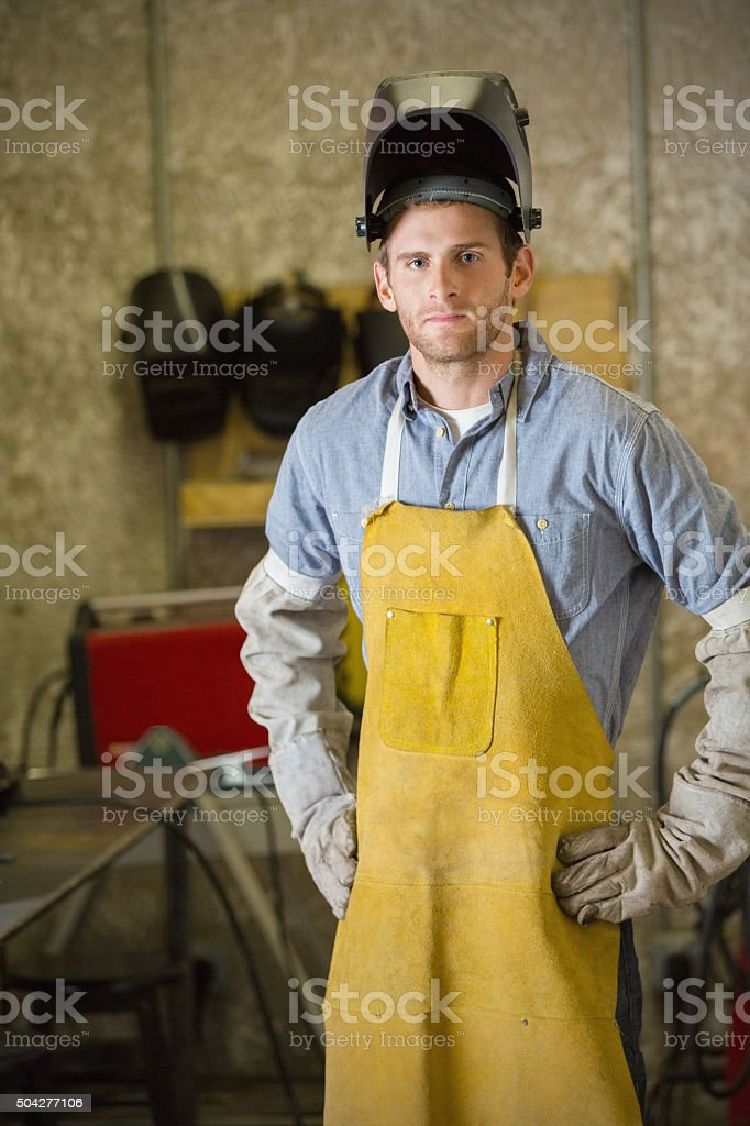 Professional welder working on metal project in shop stock photo