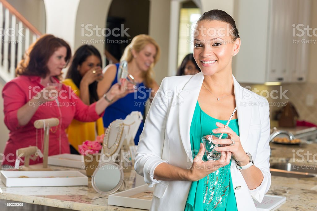 Professional woman attending direct sales home jewelry party stock photo