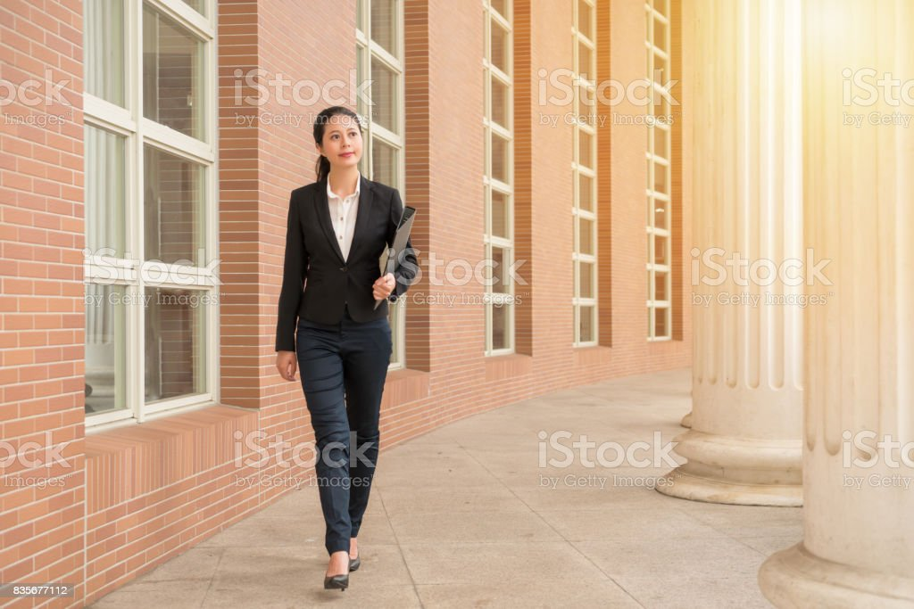 professional woman lawyer walking in court outdoor stock photo