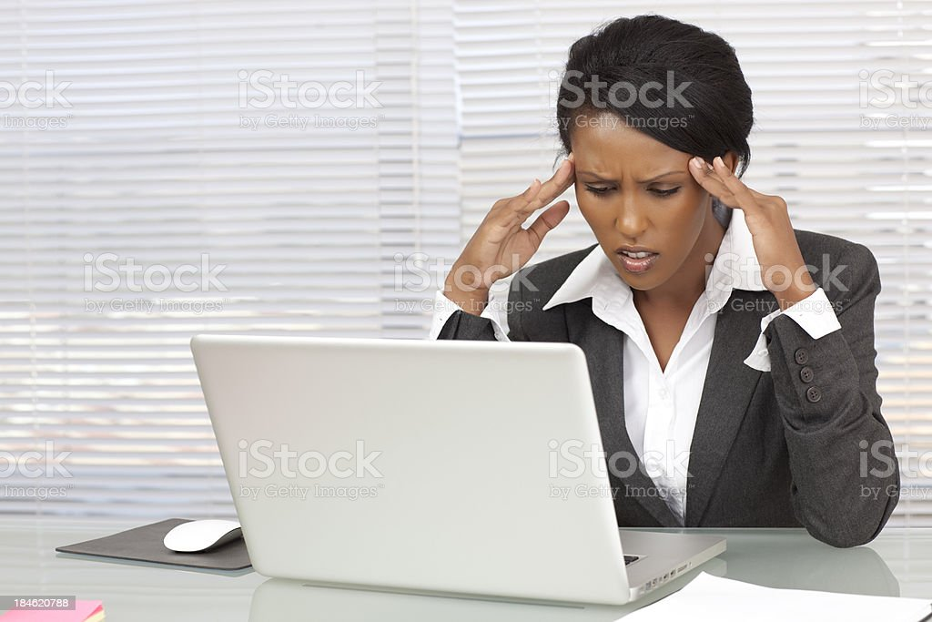 Professional woman with headache looks at laptop royalty-free stock photo