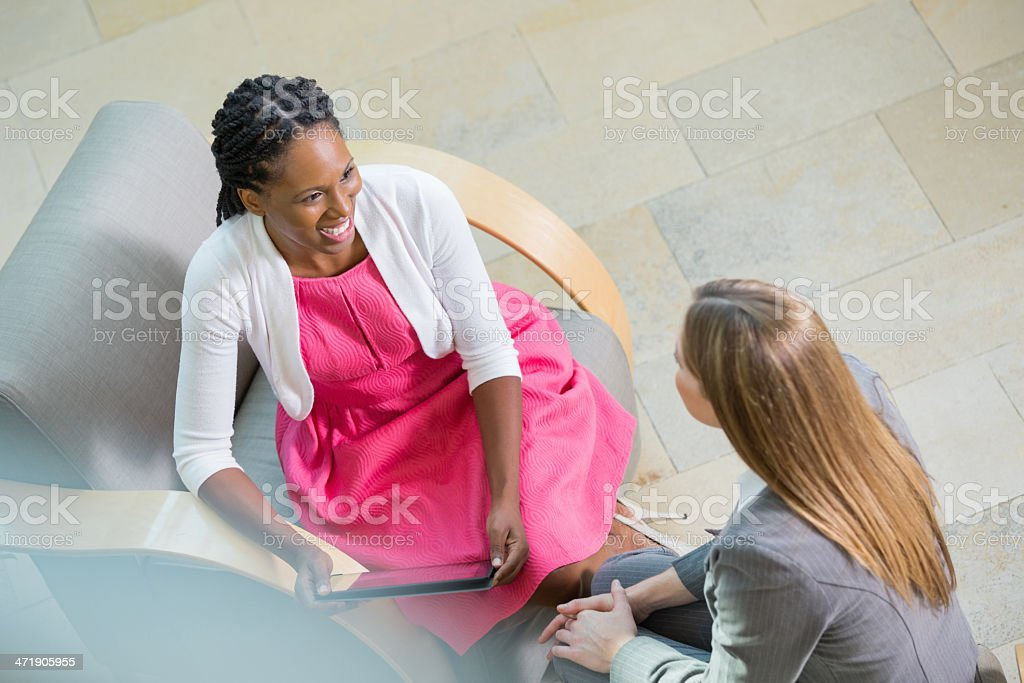Professional women discussing something in office lobby stock photo