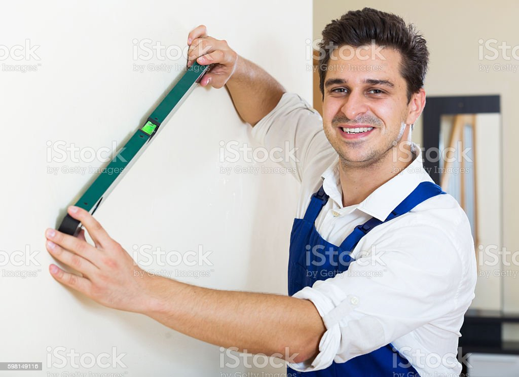 Professional worker with spirit level at wall stock photo