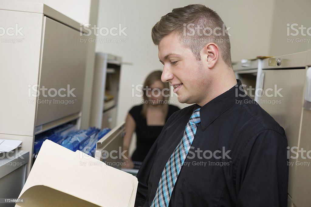 Professional young adults working in office mail or file room royalty-free stock photo