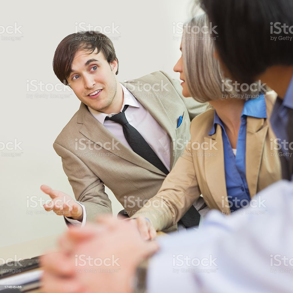 Professional young  businessman pitching ideas to colleagues in board room royalty-free stock photo