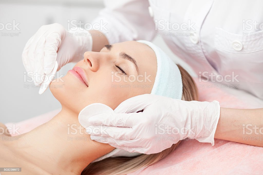 Professional young cosmetologist is curing female skin stock photo