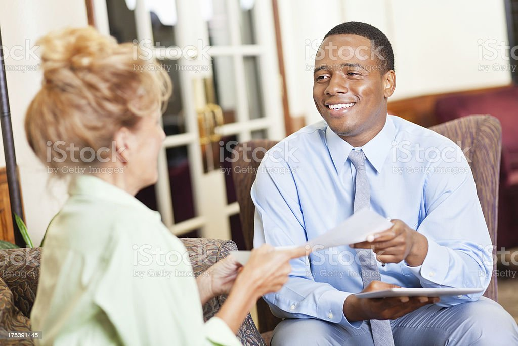 Professional young man receiving resume from woman applying for job stock photo