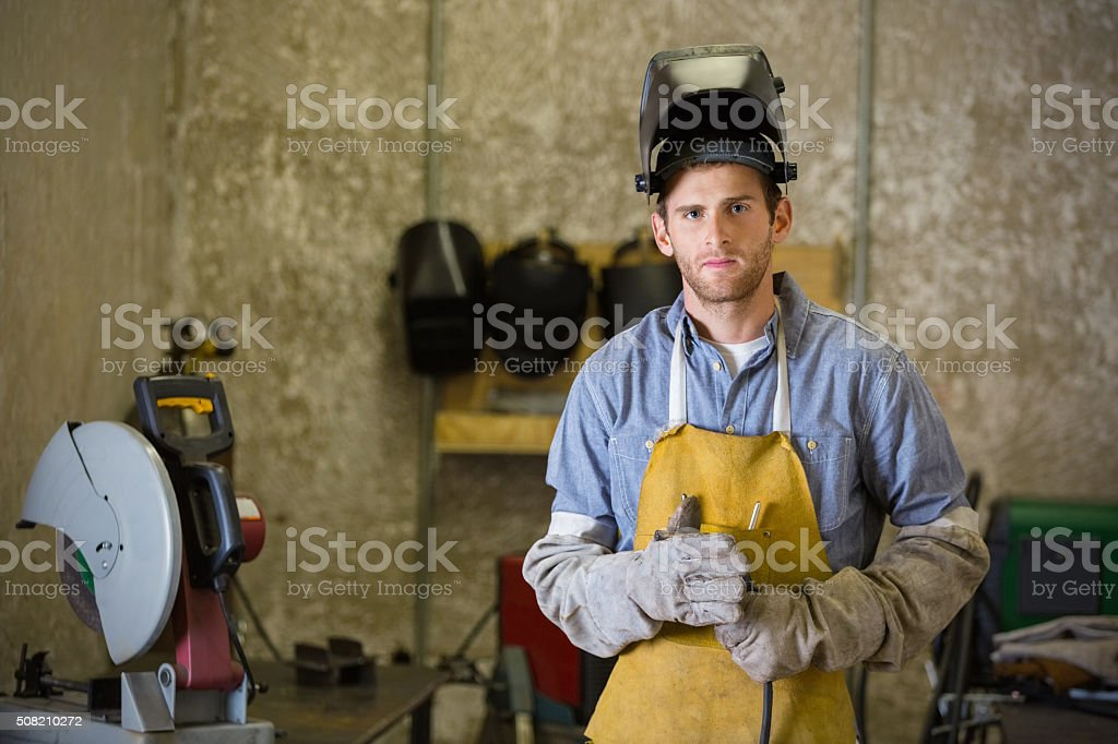 Professional young man working as welder in metal shop stock photo