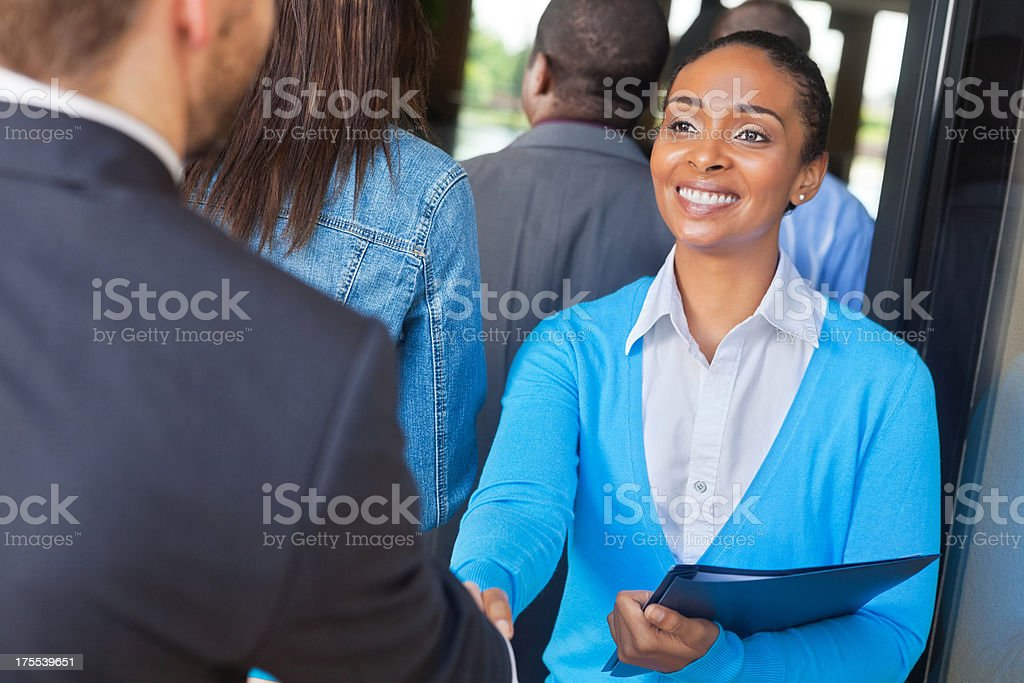 Professional young woman greeting people attending job interviews royalty-free stock photo