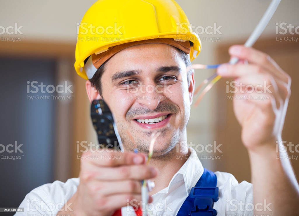 Professionalhandyman in helmet working with wires stock photo