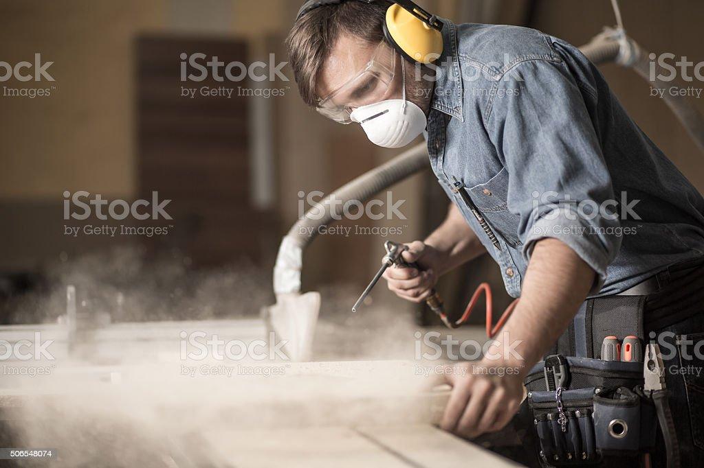 Professionally dressed carpenter varnishing board stock photo