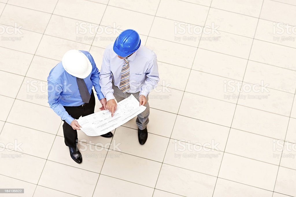 Professionals Looking Over Blueprints stock photo