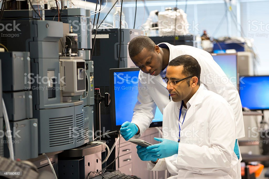 Professionals Working with Specialist Scientific Equipment for Measuring Chemicals. stock photo