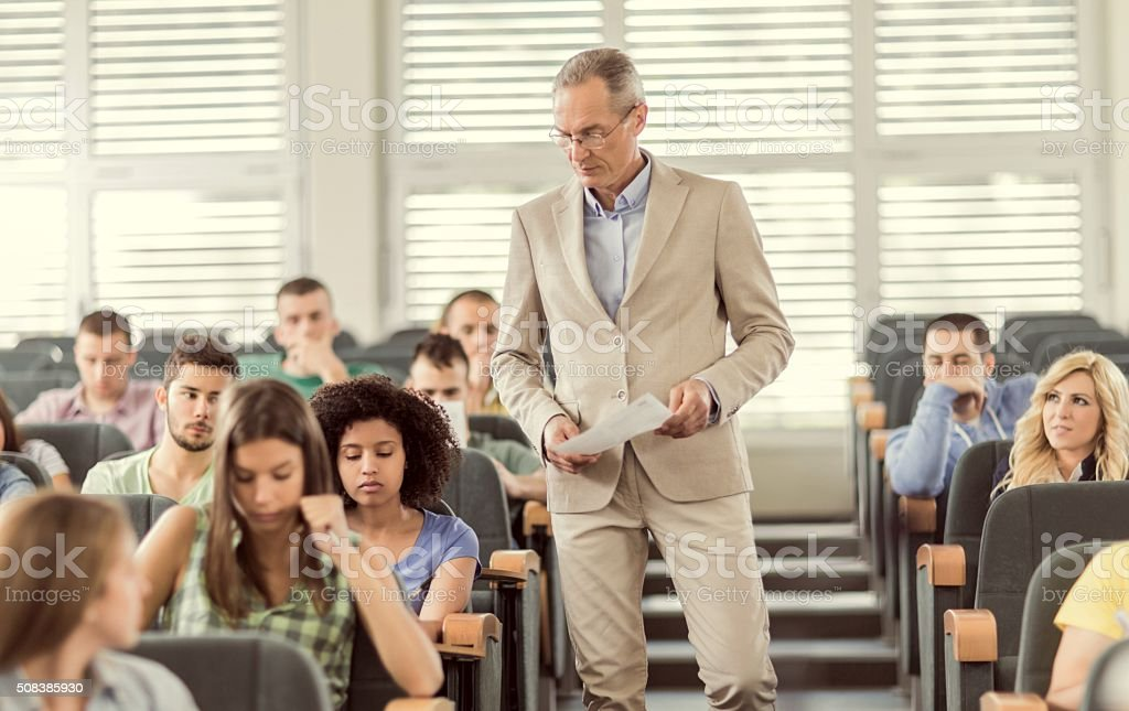 Professor and students during exam in amphitheatre. stock photo