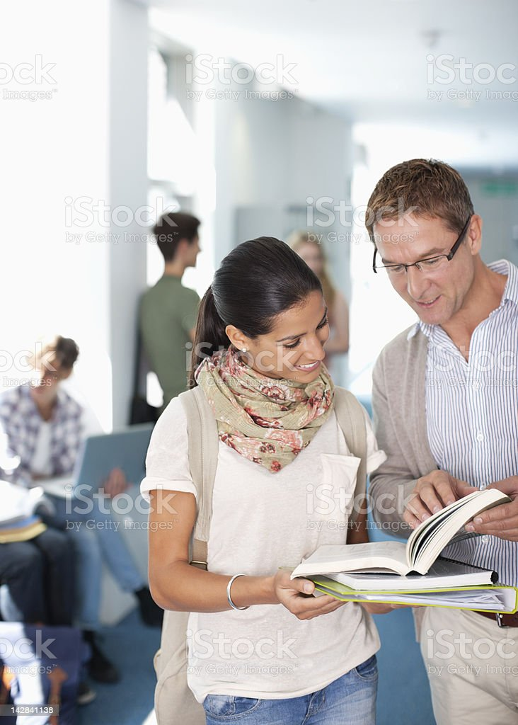 Professor and university student looking at book in corridor royalty-free stock photo