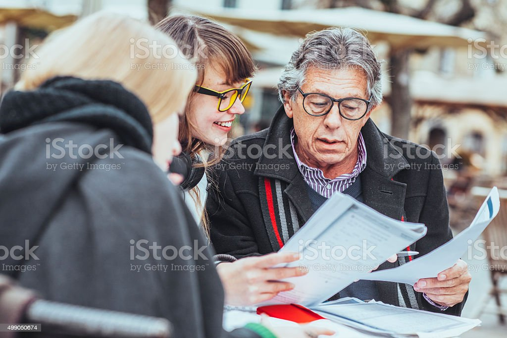 Professor and university students talking at a cafe stock photo