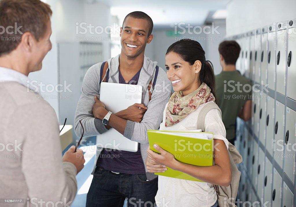 Professor and university students talking in corridor royalty-free stock photo