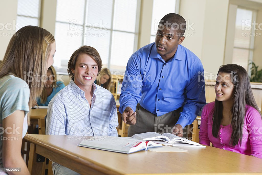 Professor assisting study group of students in high school library royalty-free stock photo