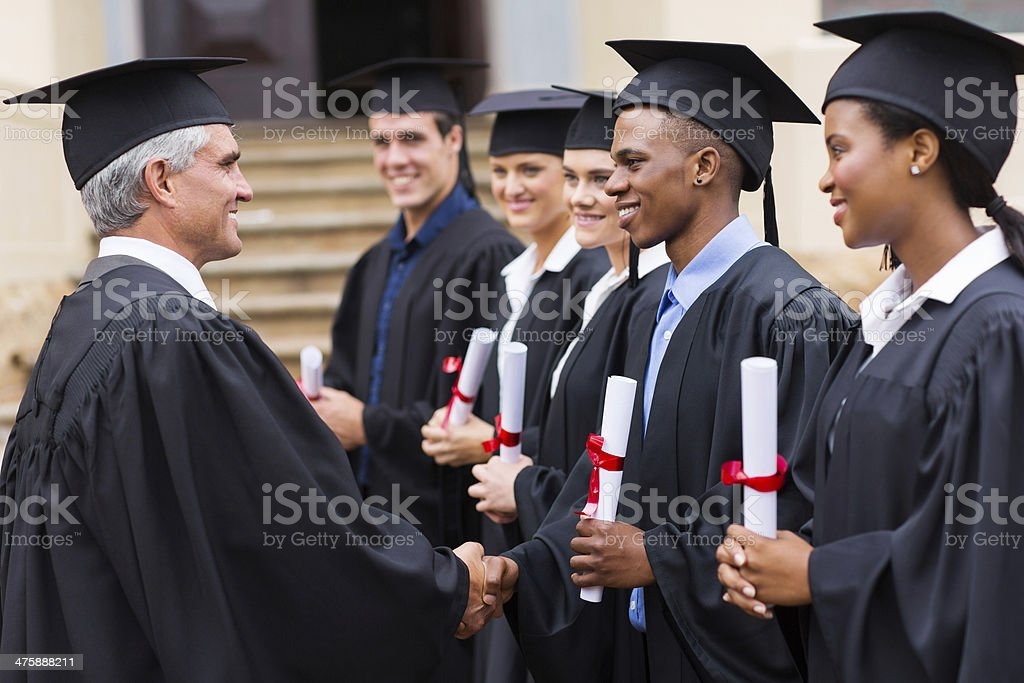 professor handshaking with graduates stock photo