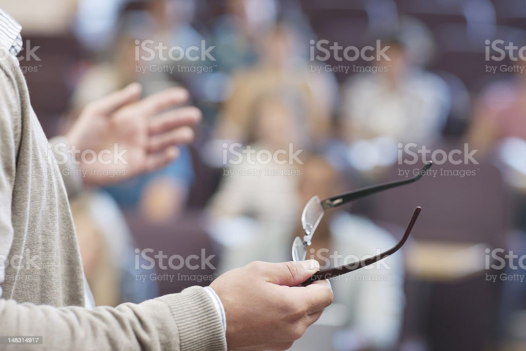 Professor holding eyeglasses and gesturing in lecture hall stock photo