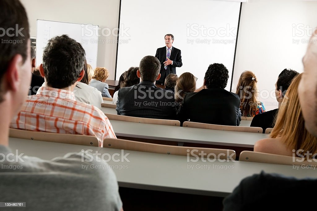 A professor teaching a business seminar to students royalty-free stock photo