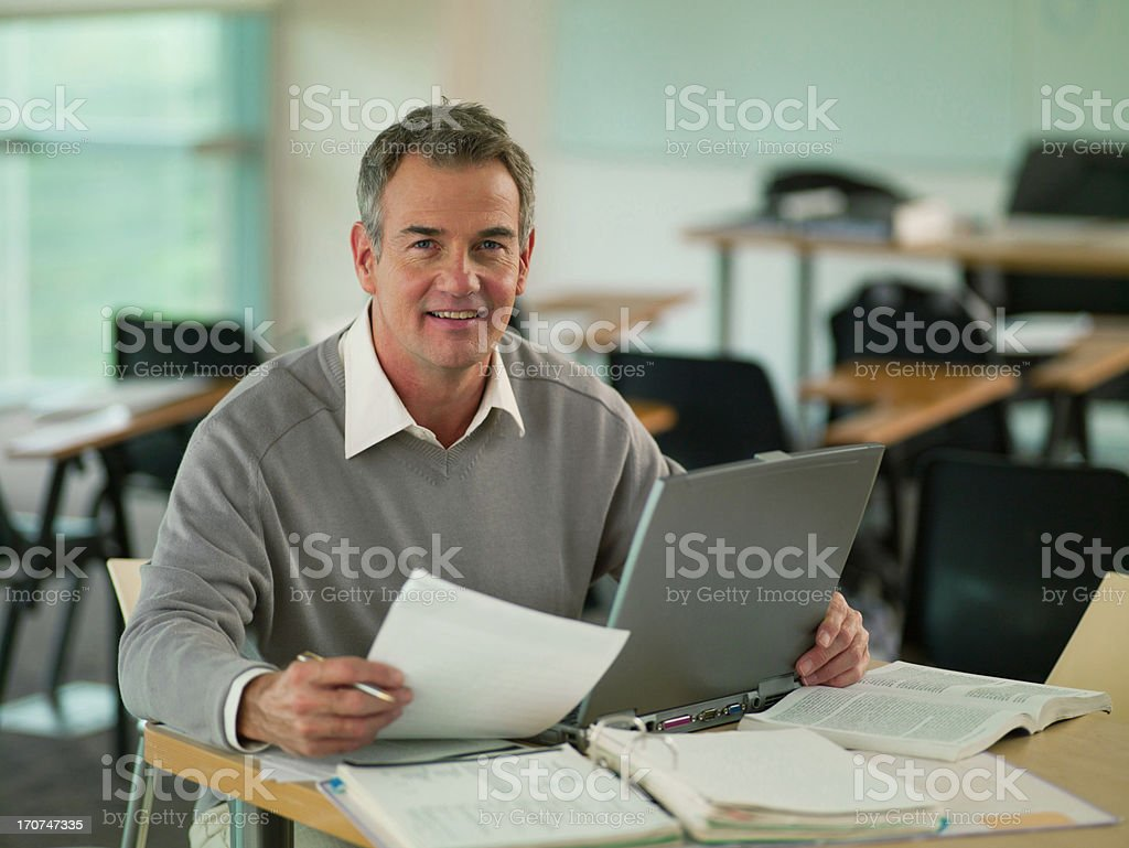 Professor using  laptop with reveiwing paperwork in classroom royalty-free stock photo