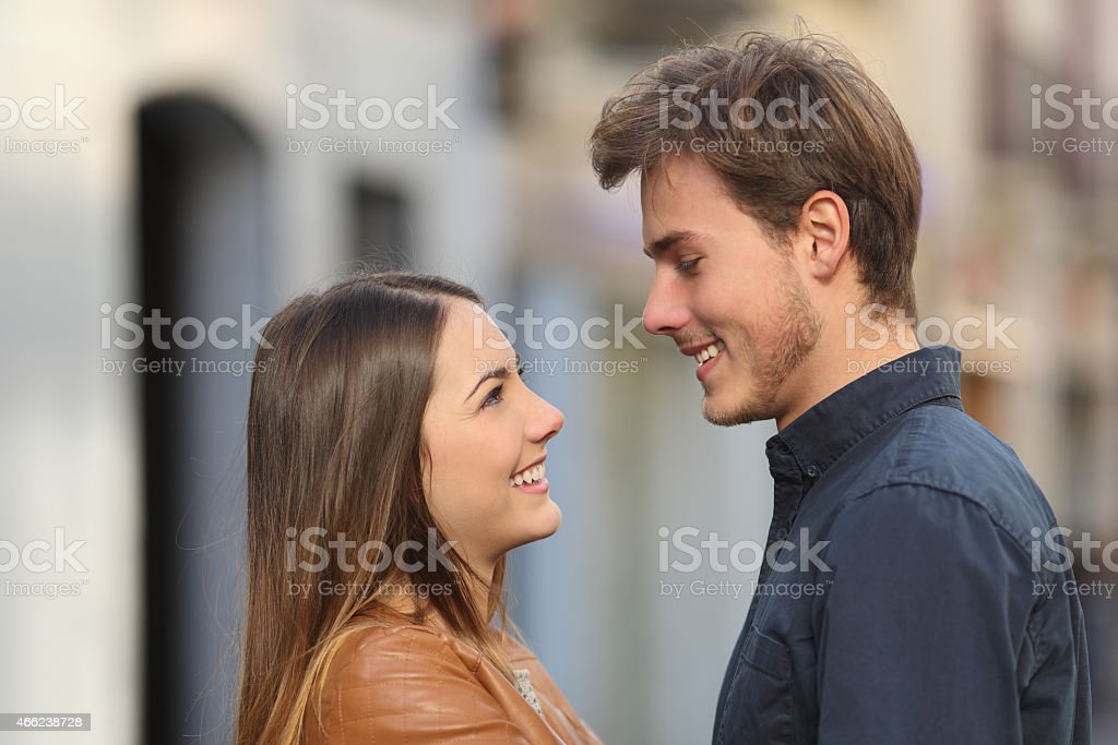Profile of a couple looking each other in the street stock photo