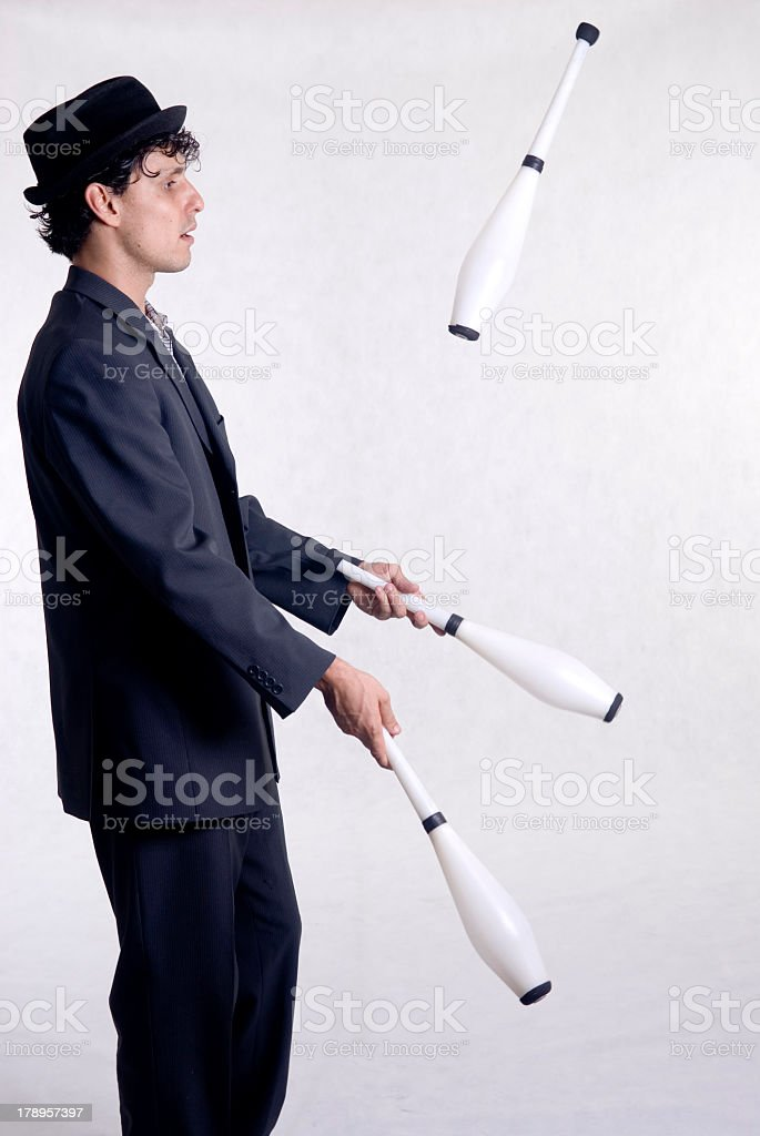 A profile of a man wearing a hat juggling bowling pins stock photo