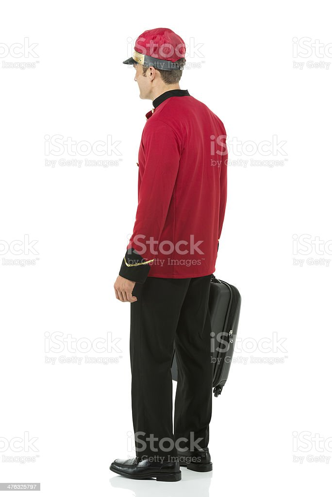 Profile of a valet standing with suitcase royalty-free stock photo