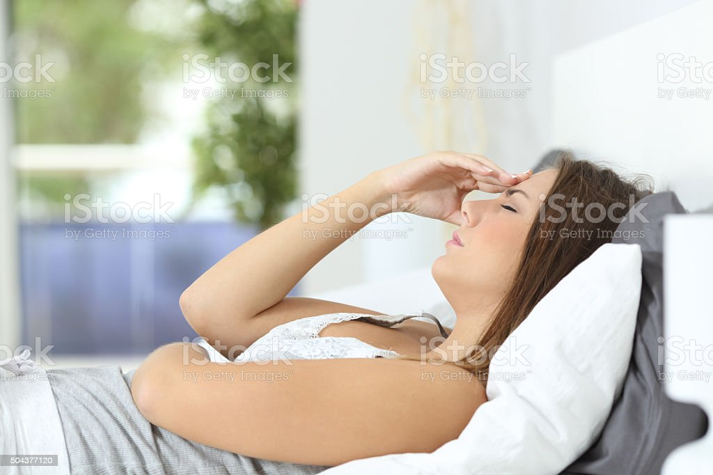 Profile of a woman suffering head ache at home stock photo