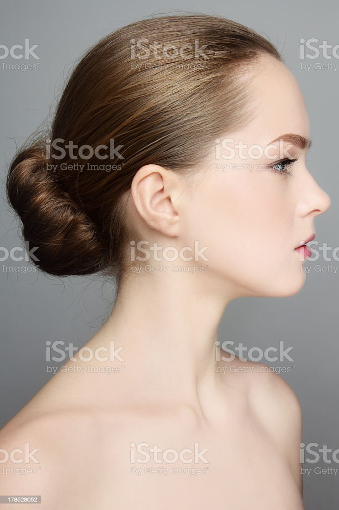 Profile of a young woman with a bun in her hair stock photo